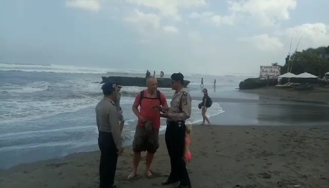 Badung sat polair talked to tourist as high tide occured at beaches in Bali.