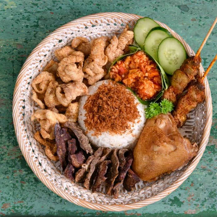 One of NasDap 's packages with rice, fried chicken skin, fried beef lung, chicken, satay, and sambal.